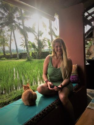 Droom-Durf-Doe-Katrín-in-groene-jurk-zit-met-rode-Kat-bij-de-rijstvelden-in-Ubud-op-Bali-