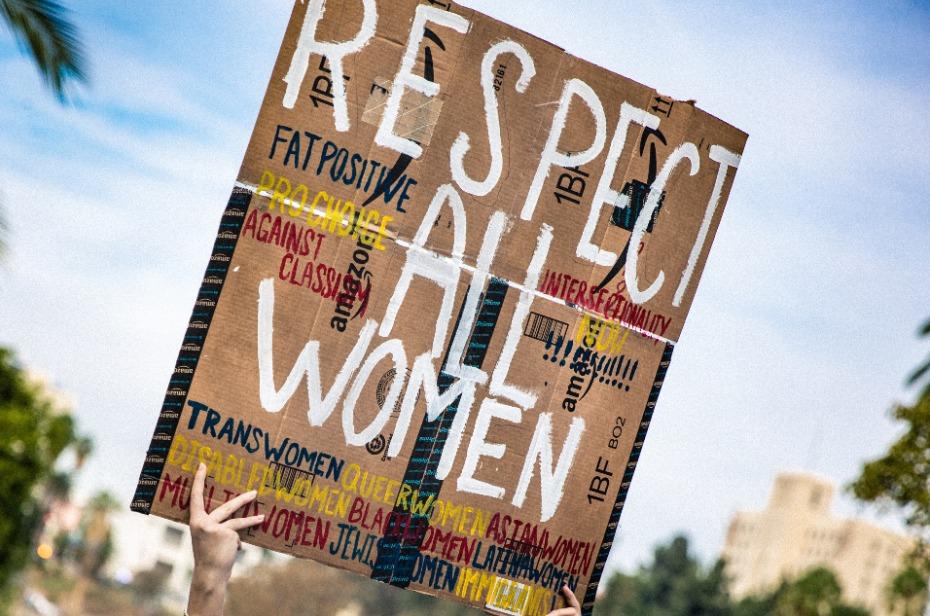 De Juf die geen Juf is. De afbeelding is een protestbord dat omhoog wordt gehouden, tijdens een demonstratie met de tekst: Respect all Women. De foto hoort bij de column Juf-ik-wil-strijden-voor-de-rechten-van-de-vrouw